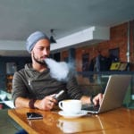 guy vaping and drinking coffee