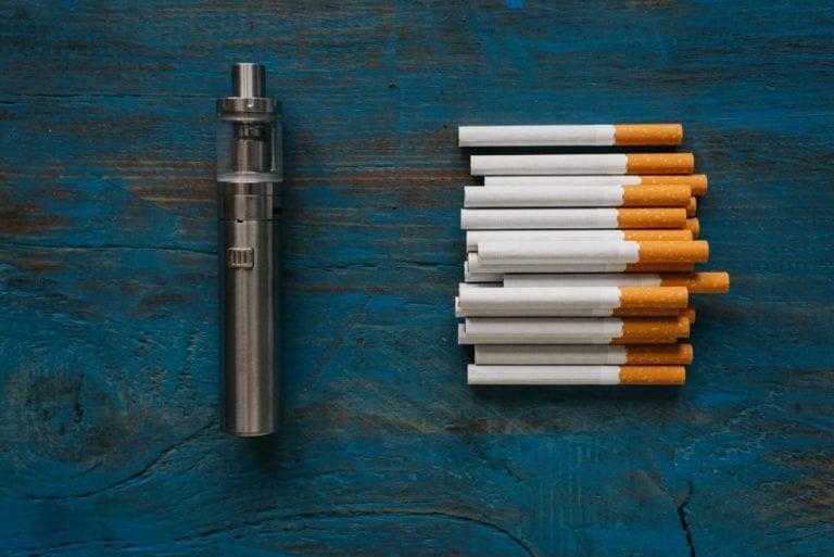 vape pen and pile of cigarettes