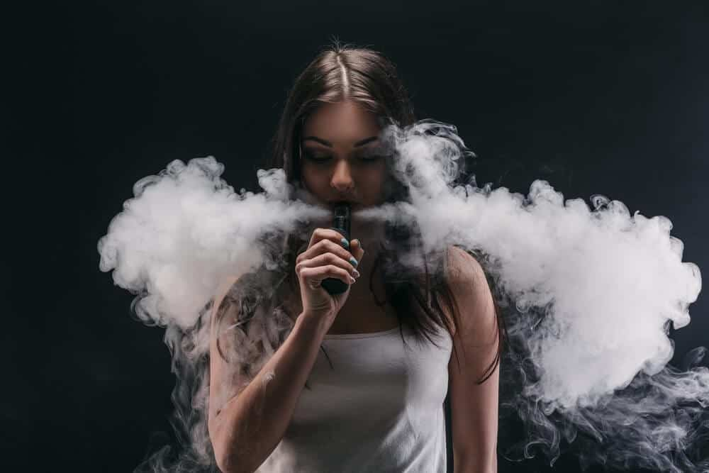 cloud chasing girl doing vape tricks image